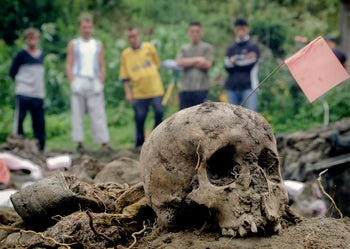 FILE - In this Thursday, July 25, 2002, file picture, a group of Bosnian Muslim villagers look at the remains of bodies exhumed from a mass grave in the village of Kamenica, Bosnia. As a U.N court prepares to hand down its verdict in the case against Ratko Mladic, the Bosnian Serb military leader during the Balkan country's 1992-5 war, the remains of numerous victims of genocide and war crimes of which he stands accused still await identification.