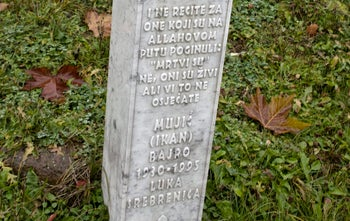 """In this Thursday, Nov. 16, 2017,photo, autumn leaves lie near a grave stone that reads """"And do not say about those who are killed in the way of Allah, They are dead. No, they are living, but you do not perceive (their existence)"""" at the memorial center of Potocari near Srebrenica, Bosnia. As a U.N court prepares to hand down its verdict in the case against Ratko Mladic, the Bosnian Serb military leader during the Balkan country's 1992-5 war, the remains of numerous victims of genocide and war crimes of which he stands accused still await identification."""
