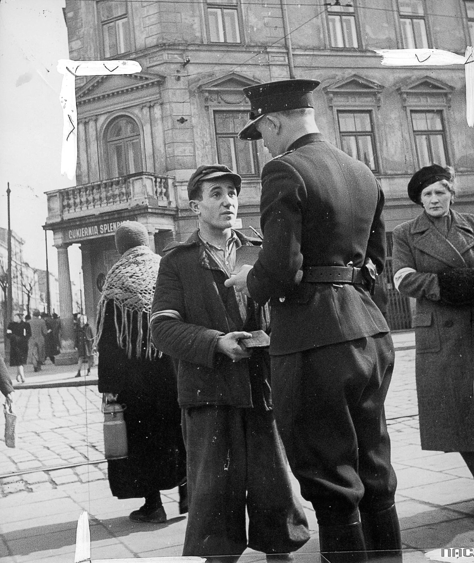 A Polish police officer checks a Jewish man's documents at the Kraków Ghetto, 1941.