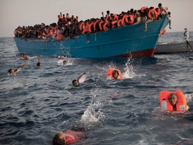 Migrants, most of them from Eritrea, jump into the water from a crowded wooden boat as they are helped a rescue operation at the Mediterranean sea near Libya, Aug. 29, 2016.