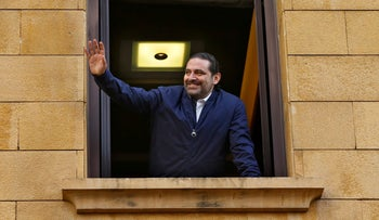 Lebanese Prime Minister Saad Hariri waves to his supporters from a window of his residence, in Beirut, Lebanon, Wednesday, Nov. 22, 2017