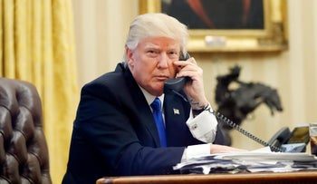 U.S. President Donald Trump speaks on the phone in the Oval Office.
