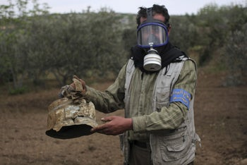 A Civil Defence member carries a damaged canister in Ibleen village from what activists said was a chlorine gas attack, on Kansafra, Ibleen and Josef villages, Idlib countryside, Syria May 3, 2015