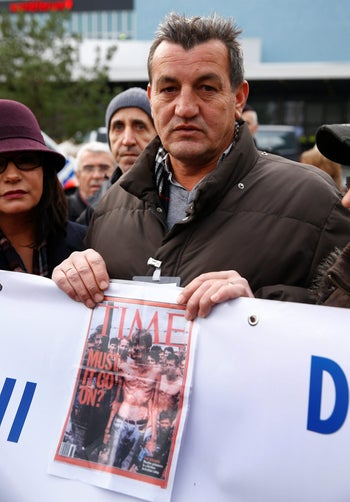 Fikret Alic, one of the survivors of Serbian concentration camps shows his photo on the cover of Time magazine outside the Mladic genocide trial in The Hague, Netherlands. November 22, 2017