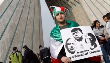 An Iranian man poses with a placard during a rally marking the anniversary of the 1979 Islamic revolution on February 10, 2017, in the capital Tehran.