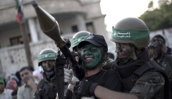 A Palestinian youth carries a rocket propelled grenade launcher during a graduation ceremony as part of a military-style summer camp organized by the Iz al-Din al-Qassam, the armed wing of Hamas, August 2015.