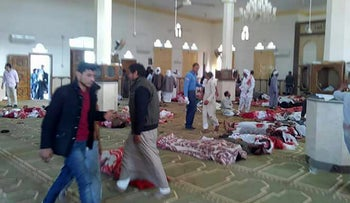 Egyptians walk past bodies following a gun and bombing attack at the Rawda mosque, roughly 40 kilometers west of the North Sinai capital of El-Arish, on November 24, 2017.
