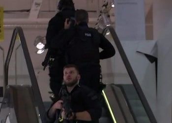 In this grab taken from video, armed police patrol a department store, near to Oxford Street, in London, Friday, Nov. 24, 2017.
