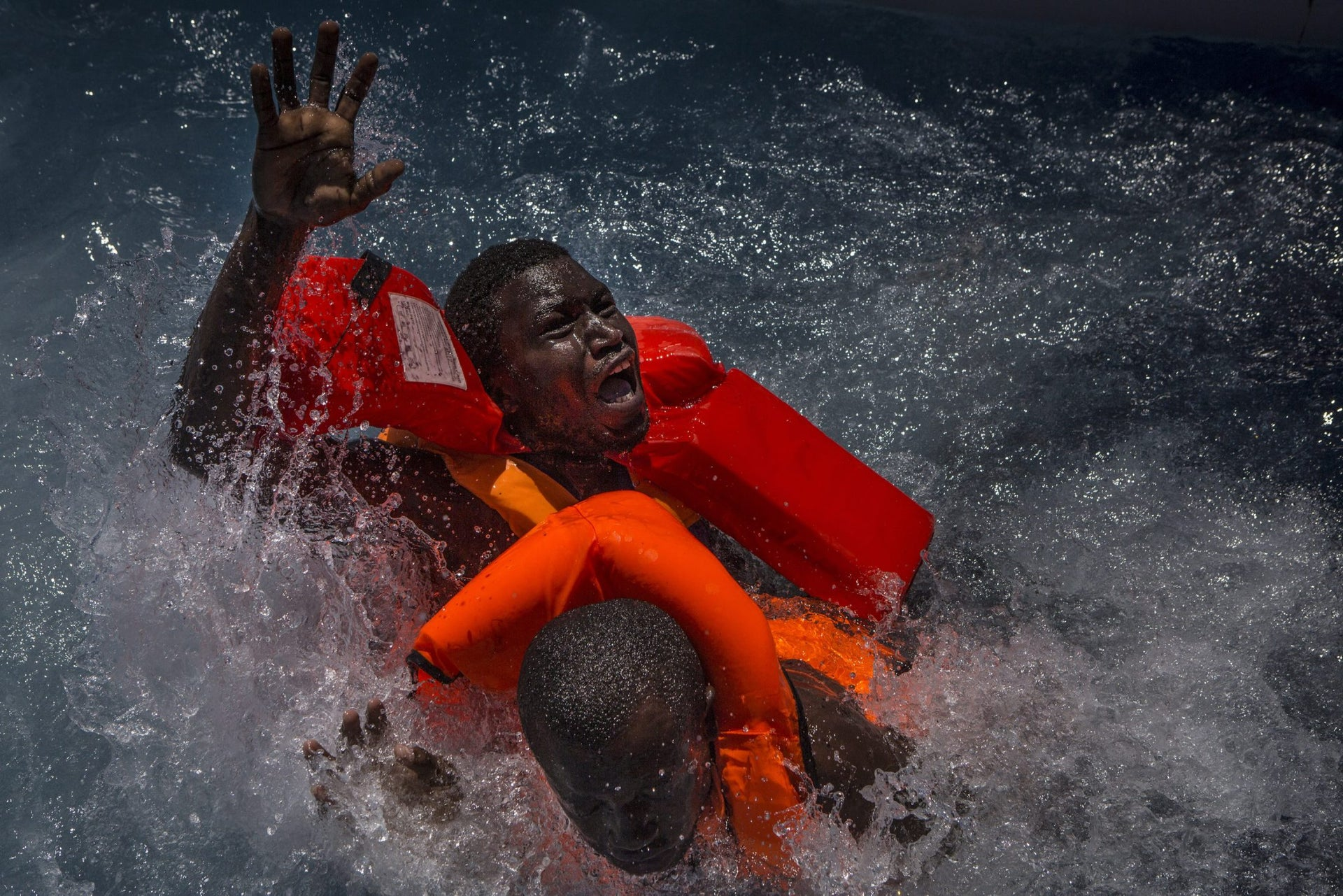 Spot News, third prize stories - Two men panic and struggle in the water during their rescue. Their rubber boat was in distress and deflating quickly on one side, tipping many migrants in the water. They were quickly reached by rescue swimmers and brought to safety.