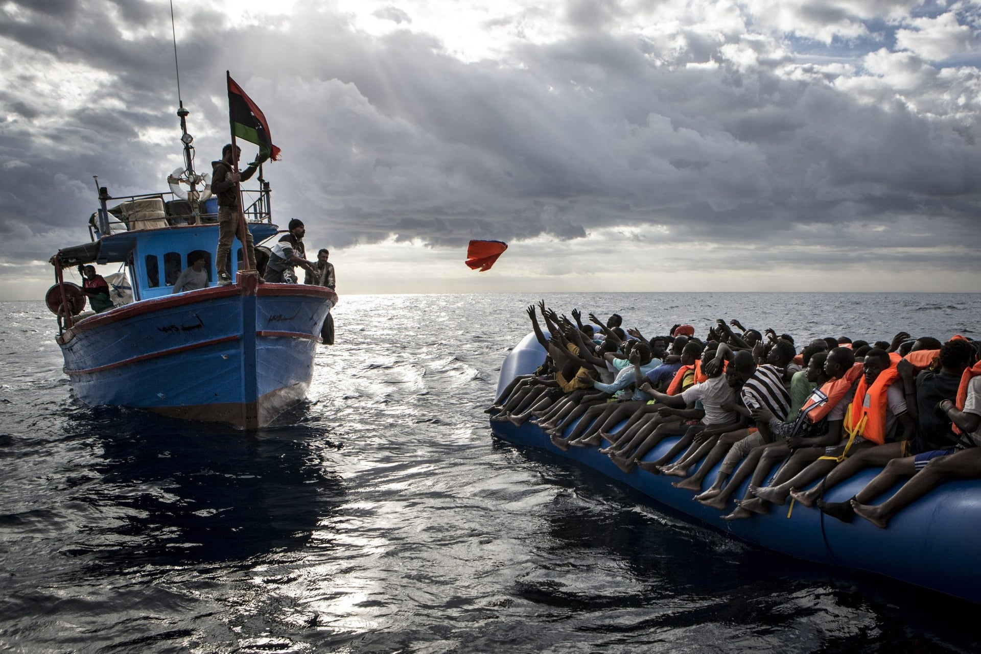 Spot News, third prize stories - Libyan fishermen throw a life jacket at a rubber boat full of migrants.