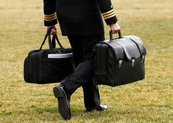 """A military aide, carrying the """"football"""" containing launch codes for nuclear weapons, accompanies U.S. President Donald Trump onto Marine One upon Trump's departure from the White House in Washington, U.S. February 3, 2017."""