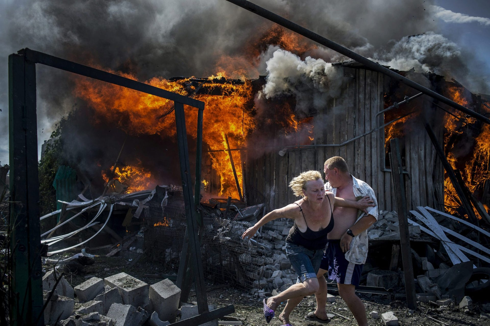 Long-Term Projects, first prize stories - Civilians escape from a fire at a house destroyed by an air attack in the Luhanskaya village.