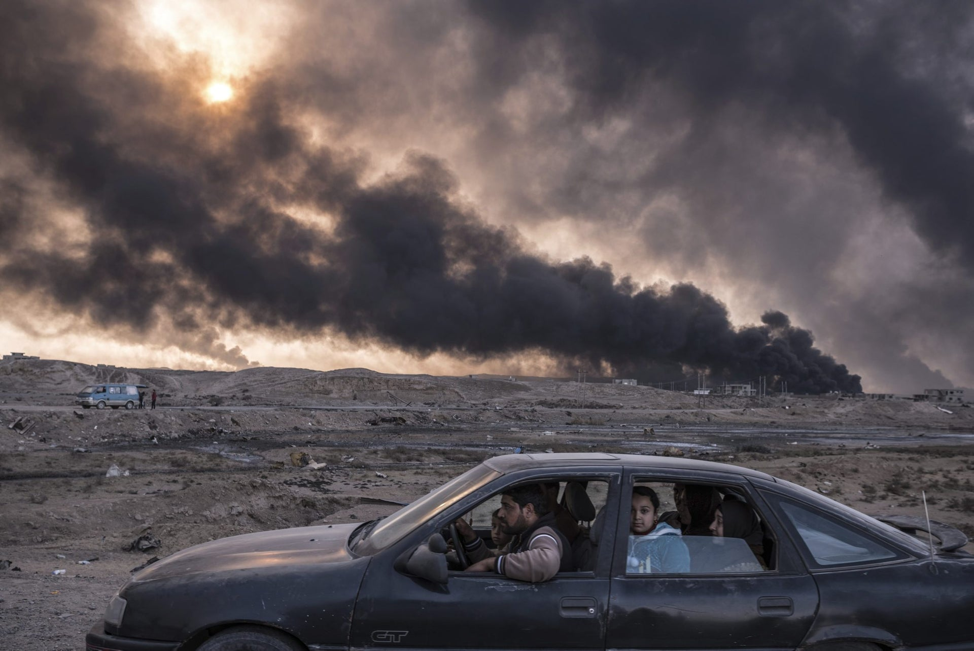 General News, second prize stories - A family flees the fighting in Mosul, Iraq's second-largest city, as oil fields burned in Qayyara, Iraq.