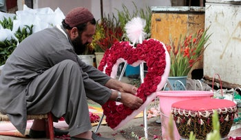 A man arranges a heart-shaped bouquet at a flower market in Islamabad, Pakistan February 14, 2017.
