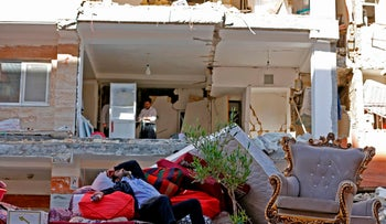 FILE PHOTO: An Iranian man rests as he lies atop salvaged mattresses and items outside damaged buildings on November 14, 2017, following a 7.3-magnitude earthquake that left hundreds killed