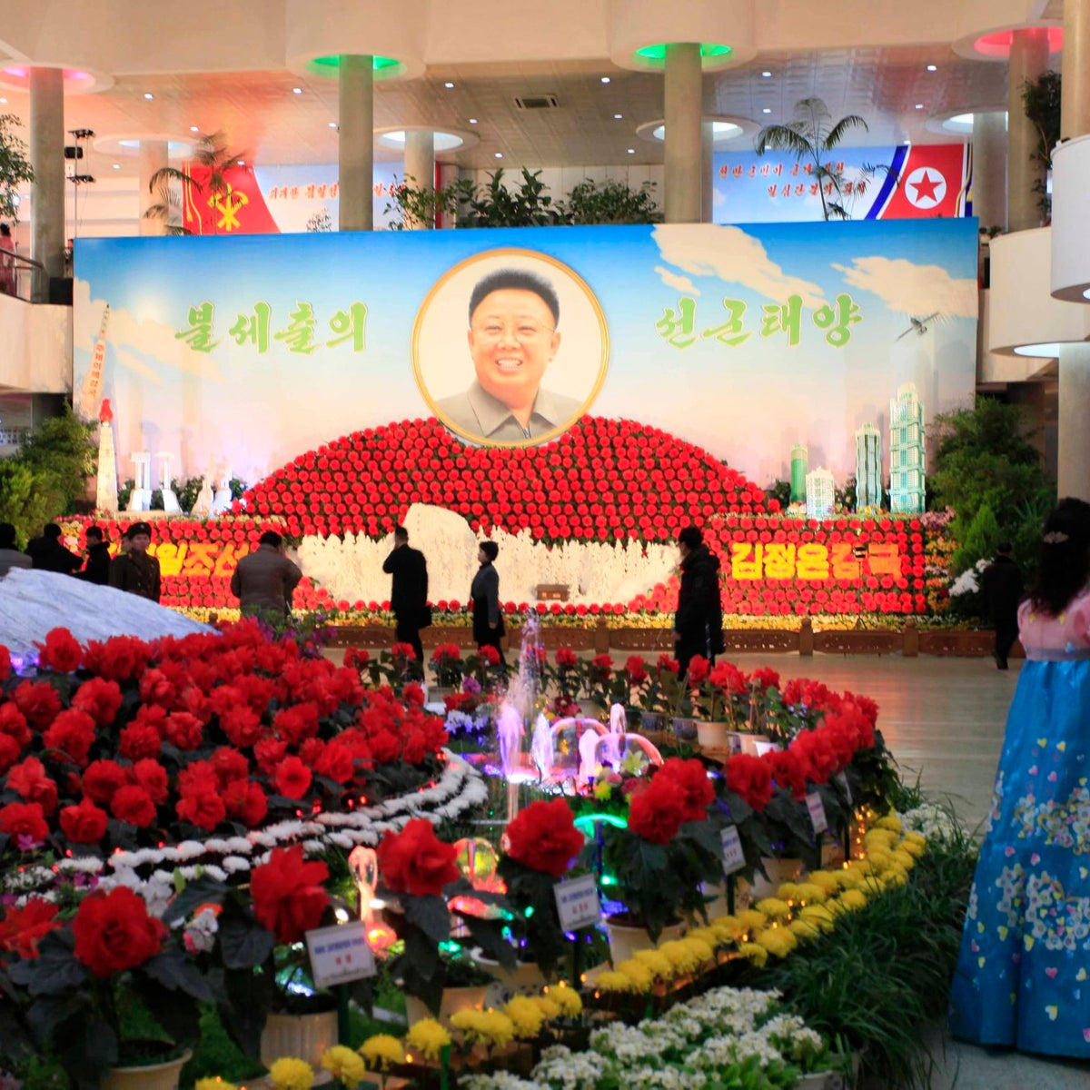 People stand near displays of flowers named after the late North Korean leader Kim Jong Il at a flower show to mark his birthday in Pyongyang, North Korea, Tuesday, Feb. 14, 2017. The annual event kicks off several days of celebrations in the North and this year also featured a depiction of the country's latest missile, which it test-launched on Sunday despite international sanctions. Kim's portrait is seen in the background.