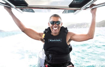 Former U.S. President Barack Obama sits on a boat during a kite surfing outing with British businessman Richard Branson in the British Virgin Islands, February 7, 2017.