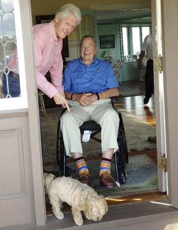 In this Sept. 5, 2013 photo, former President Bill Clinton, left, points to western cactus-themed socks worn by former President George H.W. Bush at Bush's home in Kennebunkport, Maine.