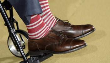 Former President George H. W. Bush, in a pair of red and white socks, participates in an award ceremony with President Barack Obama at the White House, July 15, 2013.