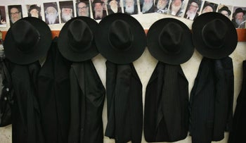Hats and jackets belonging to ultra-Orthodox Jews, with photos of rabbis above.