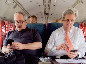 U.S. Secretary of State John Kerry and Jordanian Foreign Minister Nasser Judeh sit aboard a Royal Jordanian Air Force transport plane on February 21, 2016.