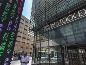 A large digital ticker shows financial information to pedestrians outside the entrance to the Tel Aviv Stock Exchange (TASE) in Tel Aviv, Israel, on Thursday, Aug. 4, 2016.