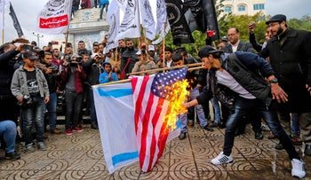 Palestinian demonstrators burn representations of Israeli and American flags during a protest against the possible U.S. decision to recognize Jerusalem as Israel's capital, in Gaza City, Wednesday, Dec. 6, 2017