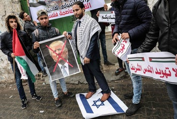 Palestinian protesters prepare to burn a picture of US President Donald Trump in the southern Gaza Strip town of Rafah on December 6, 2017.