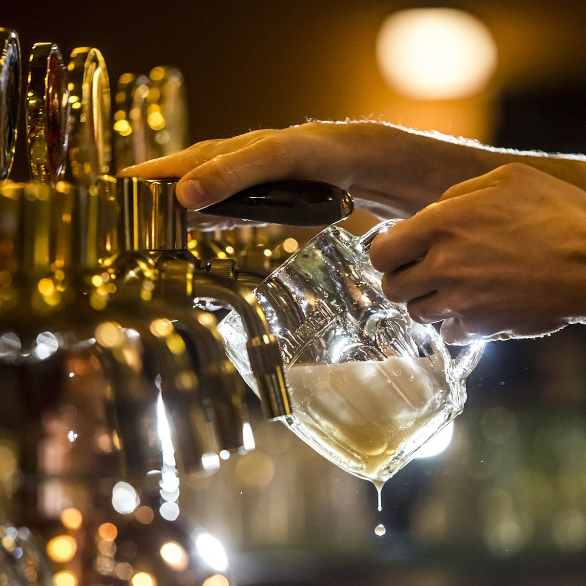 A barman pours a glass of beer from a tap (illustrative).