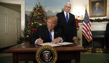 U.S. President Donald Trump signs a memorandum after he delivered a statement on Jerusalem on December 6, 2017 as U.S. Vice President Mike Pence looks on.