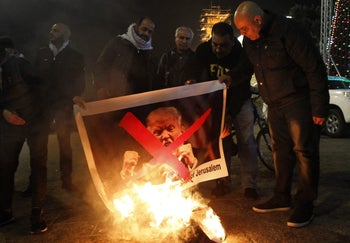 Palestinian protesters burn pictures of US President Donald Trump at the manger square in Bethlehem on December 5, 2017.