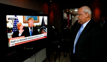 Chief Palestinian negotiator Saeb Erakat watches a speech given by U.S. President Donald Trump on Jerusalem at his residence in the West Bank city of Jericho, December 6, 2017.