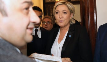 France's far-right presidential candidate Marine Le Pen reacts upon being handed a headscarf before her meeting with Lebanon's Grand Mufti in Beirut on February 21, 2017.