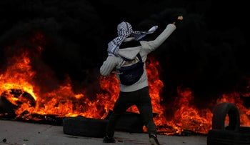 A Palestinian protester hurls stones towards Israeli troops during clashes at a protest against Trump's decision to recognize Jerusalem as the capital of Israel, near the West Bank city of Ramallah December 7, 2017.