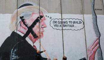 A Palestinian painting over a mural of U.S. President Donald Trump during a protest in Bethlehem, West Bank, December 7, 2017.