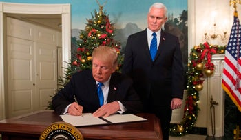U.S. President Donald Trump signing a proclamation after delivering his statement on Jerusalem in the White House, Washington, on December 6, 2017, as Vice President Mike Pence looks on.