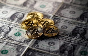 FILE PHOTO: Bitcoin (virtual currency) coins placed on Dollar banknotes are seen in this illustration picture, November 6, 2017.
