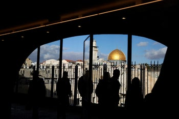 People look out from a building facing the Dome of the Rock (R), located in Jerusalem's Old City on the compound known to Muslims as Noble Sanctuary and to Jews as Temple Mount December 7, 2017.