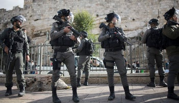 Israeli police officers stand guard as Palestinian women protest outside the Damascus Gate in Jerusalem Old City, Thursday, Dec. 7, 2017. Clashes between hundreds of Palestinian protesters and Israeli troops erupted across the West Bank on Thursday while demonstrators in Gaza burned posters of President Donald Trump and Israeli Prime Minister Benjamin Netanyahu, as well as Israeli and U.S. flags.