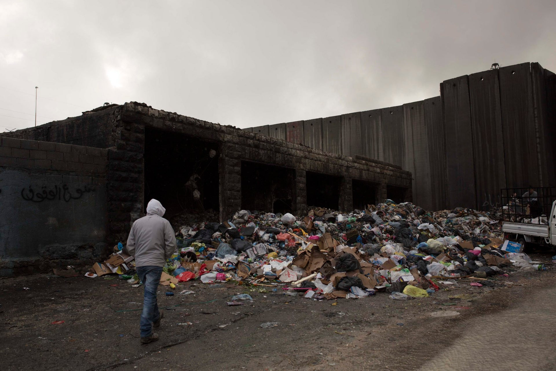 """A man walking past trash at the entrance to the Shoafat refugee camp. Although Israel annexed the camp after the Six-Day War in 1967, it is now on the """"wrong side"""" of the West Bank separation barrier."""