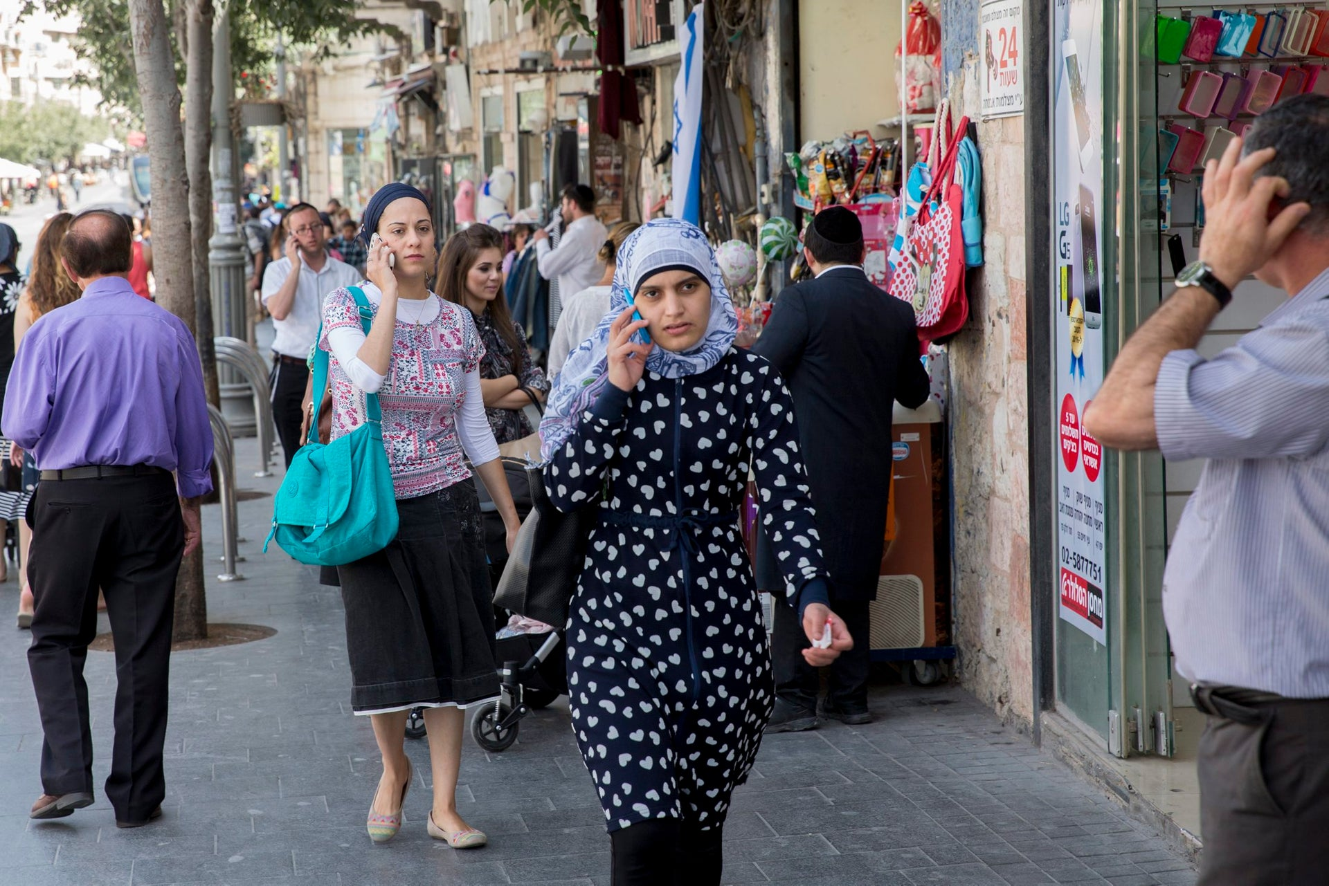 A Jewish and Arab woman talking on cellphones in Jerusalem, June 2016. Some 324,000 of the city's 865,000 residents are Arab.