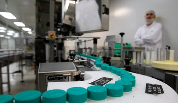 File photo: An employee of Teva Pharmaceutical Industries watches pill bottles on a conveyor belt at the company's Jerusalem oral solid dosage plant.