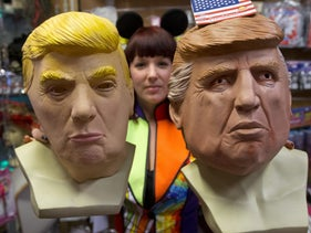 An employee at a store in Amsterdam holds two masks of U.S. President Donald Trump, February 22, 2017.