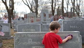 Theo Richmond cleaning a headstone at the Chesed Shel Emeth Cemetery in University City, on February 22, 2017.