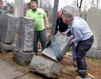Workmen righting toppled Jewish headstones after a weekend vandalism attack on Chesed Shel Emeth Cemetery in University City, Missouri, February 22, 2017.