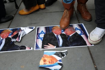 Demonstrators walk over images of US President Donald Trump and Israeli PM Benjamin Netanyahu as they take part in a protest in Paris on December 9, 2017