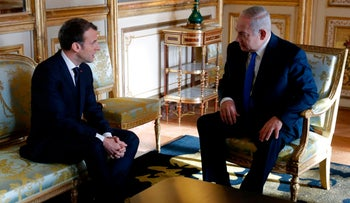 French President Emmanuel Macron speaks with Prime Minister Benjamin Netanyahu ahead of a meeting at The Elysee Palace in Paris on December 10, 2017.
