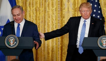 U.S. President Donald Trump reaches out for Prime Minister Benjamin Netanyahu during a news conference in the White House, February 15, 2017.