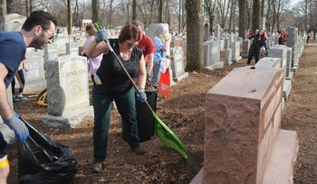 Volunteers help during a cleanup effort at Chesed Shel Emeth Cemetery, Missouri, February 22, 2017.