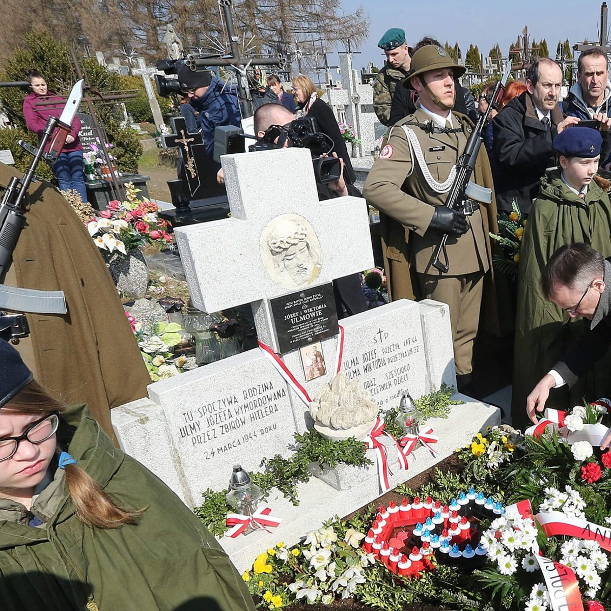 Soldiers stand guard at the flower-covered grave of the Ulma family, a couple with six small children, who were killed by the Germans in 1944 for sheltering eight Jews, who were also killed with the family, during remembrance ceremonies at the cemetery in Markowa, Poland, Thursday, March 17, 2016.